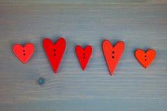 Rote Herzen auf grauem hölzernem Hintergrund Knopfliebe Stockfoto