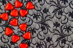 Rote Herzen auf schwarzer Spitze Stockfotografie