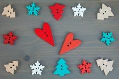 Rote Herzen, Bäume und Schneeflocken auf grauem hölzernem Hintergrund Stockbild