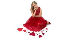 Rote Herzen der blonden Frau, die den Valentinsgruß lokalisiert sitzen Stockbilder
