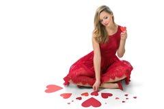 Rote Herzen der blonden Frau, die den Valentinsgruß lokalisiert sitzen Lizenzfreies Stockbild
