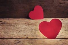 Rote Herzen des Valentinstags auf Holztisch Stockbilder