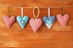 Rote Herzen, die über grauem hölzernem Hintergrund hängen Lizenzfreie Stockfotografie