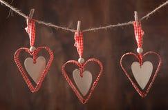 Rote Herzen, die über hölzernem Hintergrund hängen lizenzfreie stockbilder