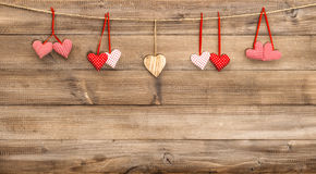Rote Herzen, die am hölzernen Hintergrund hängen Rote Rose Stockfoto