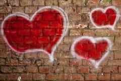 Rote Herzen gemalt auf einer Backsteinmauer Lizenzfreie Stockfotos