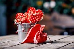 Rote Herzen im Zink schöpfen auf hölzernem Hintergrund in der Weinlese und im Retrostil Rote Rose und Inneres über Weiß Lizenzfreie Stockbilder