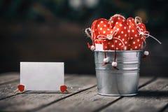 Rote Herzen im Zink schöpfen auf hölzernem Hintergrund mit Papierkarte in der Weinlese und im Retrostil Rote Rose und Inneres übe Stockfoto
