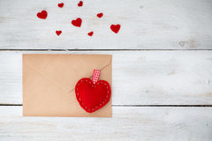 Rote Herzen liegen mit einem Umschlag auf einem weißen hölzernen Hintergrund Lizenzfreie Stockbilder