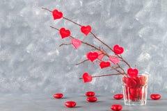 Rote Herzen mit einer Aufschrift Liebe hängen an den Niederlassungen auf einem grauen konkreten Hintergrund Vektornachricht getre Stockfoto