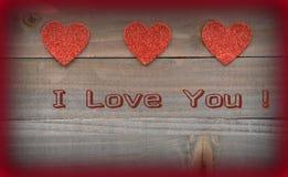 Rote Herzen mit ich liebe dich an hölzernem Hintergrund Stockfoto
