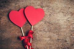 Rote Herzen mit rotem Band auf Holztisch Stockbilder