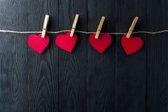 Rote Herzen mit Wäscheklammern auf dunklem Hintergrund Stockfotografie