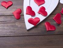 Rote Herzen nahe bei einem weißen Herzen auf braunem Holztisch Lizenzfreies Stockfoto