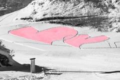 Rote Herzen schnitzten im Schnee als Gruß eines Heiligvalentinsgrußes Stockbild