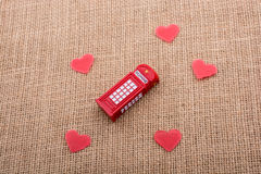 Rote Herzen um rote Farbtelefonzelle Lizenzfreie Stockfotos