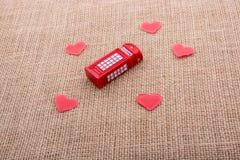Rote Herzen um rote Farbtelefonzelle Lizenzfreie Stockbilder