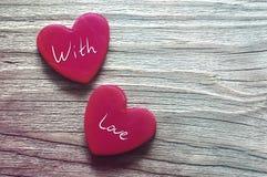 Rote Herzen und das Text ` mit Liebe ` Zwei rote Herzen auf einem hölzernen alten Hintergrund Romantische Karte Stockbilder