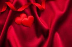 Rote Herzen und Seide Stockbild