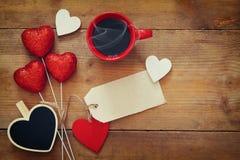Rote Herzen und Tasse Kaffee auf hölzernem Hintergrund Lizenzfreie Stockfotos