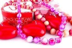 Rote Herzkerzen, -halsketten und -Geschenkboxen Stockfotografie