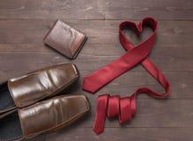 Rote Herzkrawatte, -geldbörse und -schuhe sind auf hölzernem Hintergrund Lizenzfreie Stockfotografie