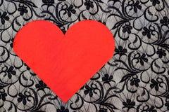 Rote Herzserviette auf schwarzer Spitze Stockfotografie