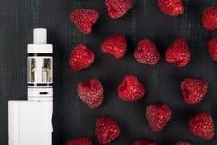 Rote Himbeeren und weiße elektronische Zigarette liegen auf einem dunklen Hintergrund lizenzfreie stockfotos