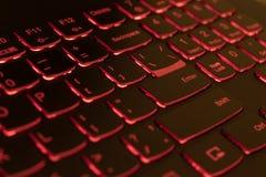 Rote hintergrundbeleuchtete Laptoptastatur, Zerhacken und blockchain Konzept lizenzfreies stockfoto