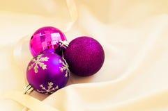 Rote Hintergrundnahaufnahme Purpurrote Weihnachtsbälle auf einem weißen Gewebe lizenzfreies stockbild