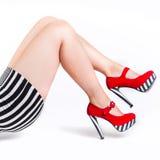 Rote hohe Absätze auf schönen weiblichen Beinen Lizenzfreie Stockfotografie