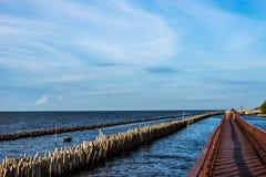 Rote Holzbrücke auf dem Ozean und dem nahen Wellenbrecher Stockbild