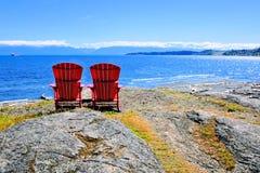 Rote Holzstühle, die den Ozean übersehen Lizenzfreies Stockfoto