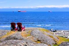 Rote Holzstühle, die den Ozean übersehen Lizenzfreies Stockbild