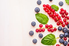 Rote Johannisbeeren, Blaubeeren und Brombeeren mit Wassertropfen und tadellose Blätter auf weißem hölzernem Hintergrund, Draufsic Lizenzfreies Stockbild