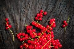 Rote Johannisbeerfrucht zerstreute Holzbanktabelle Stockfotografie