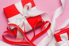Rote Kästen mit einem Geschenk, gebunden mit einem weißen Band und rote selbst gemachte Papierherzen auf einem rosa Hintergrund S stockfotografie
