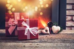 rote Kästen Weihnachtsgeschenke auf Holztisch - brennender Kamin Lizenzfreie Stockfotos