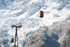 Rote Kabinen auf Skiaufzug Stockfotos