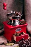 Rote Kaffeemühle auf einem Sackleinenhintergrund stockfotos