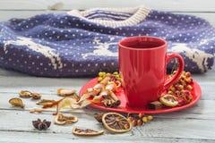 Rote Kaffeetasse auf einer Platte, hölzerner Hintergrund, Getränk, Weihnachtsmorgen Stockfotografie