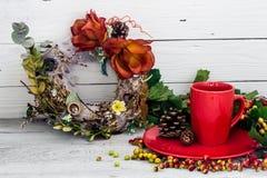 Rote Kaffeetasse auf einer Platte, hölzerner Hintergrund, Getränk, Weihnachtsmorgen Stockfotos