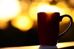 Rote Kaffeetasse, die mit einem Sonnenaufgang überläuft Stockbilder