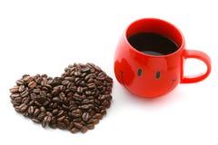 Rote Kaffeetasse- und Kaffeebohnen im Herzen formen Stockfoto