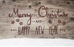 Rote Kalligraphie-frohe Weihnachten und guten Rutsch ins Neue Jahr, hölzerner Hintergrund, Schnee Stockfotos
