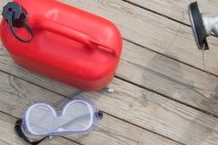 Rote Kanister mit Brennstoff für füllende Kettensägen, auf einem hölzernen Hintergrund, mit Augenschutzeinzelteilen lizenzfreie stockfotos
