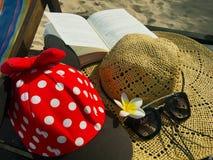 Rote Kappe mit weißen Tupfen, Strohhut, Blumen, Buch und gesungen stockbilder