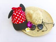 Rote Kappe mit weißen Tupfen, Strohhut, Blumen und Sonnenbrille stockbild