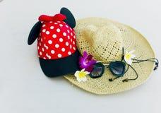 Rote Kappe mit weißen Tupfen, Strohhut, Blumen und Sonnenbrille lizenzfreies stockfoto