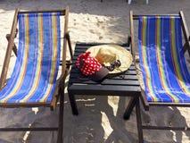 Rote Kappe mit weißen Tupfen, Strohhut, Blumen und Sonnenbrille stockbilder